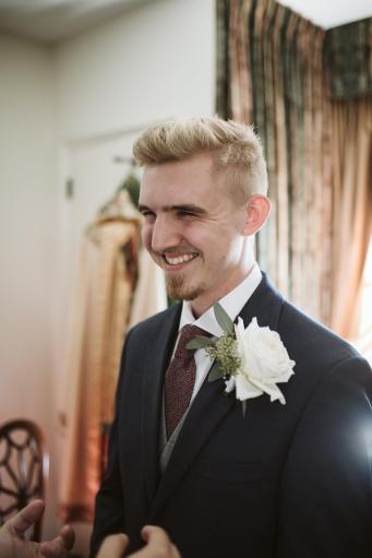 Micah Krey smiling as he waits in his suit for his wedding.